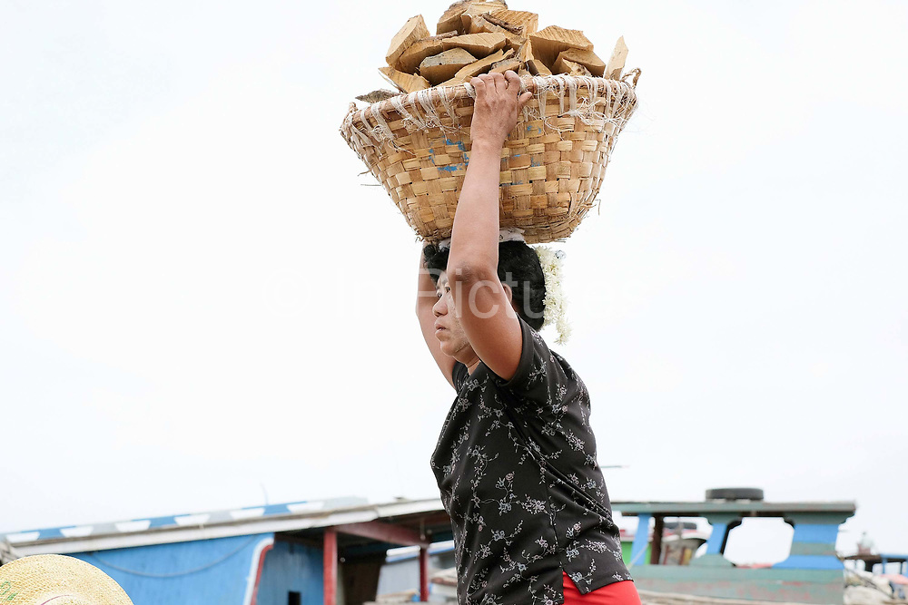A woman labourer carrying a basket of wood from a boat on the Ayeyarwady river in Mandalay on 25th May 2016 in Myanmar