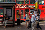 London commuters at a bus stop below a red London double-decker bus, with a Hollywood blockbuster film banner. The comedy of the movie film is echoed in the theatre on the street below where people stand around the tall post containing bus numbers and services around the capital.