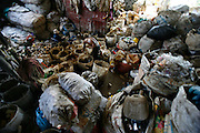 General view looking down inside of plastic recycling warehouse. The plastics are sorted by recycling workers earning less than a dollar day. They throw platsic of different textures and colours into various buckets. These are collected and placed into larger sacks. The plastic is then put through a mincer (like making minced meat for hamburgers) and the small crushed picese of plastic mixed with water in the process are then dried on mats in the sun, like for coffee beans. The dry plastic shavings are bagged and shipped off for export to Thailand and Vietnam