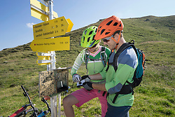Young couple of mountainbikers certificating their biketour at sign posts, Zillertal, Tyrol, Austria