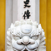 Ornately carved white marble lions guard the entrance to a gate at the One Pillar Pagoda next to the Ho Chi Minh Museum in the Da Binh district of Hanoi, Vietnam. Vietnamese characters in the background.