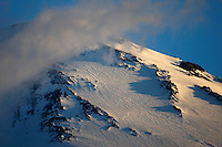 Russia, Caucasus, Mount Elbrus, highest mountain of Europe (5642 m asl), seen from Mount Cheget in the early morning. Mountains surrounded by clouds.