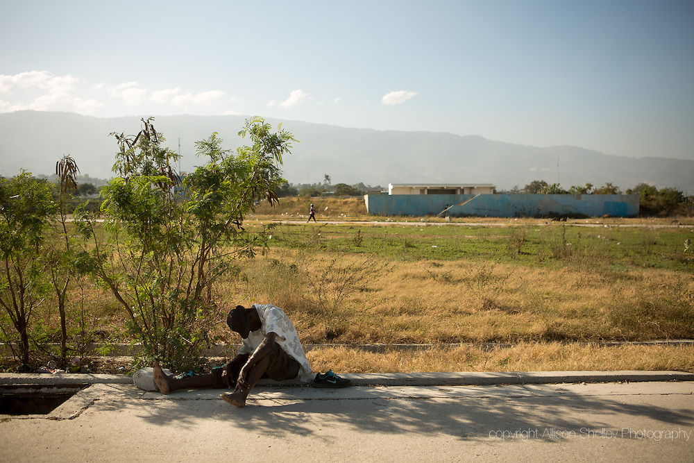 A man rests in the shade of a small bush on the grounds of the former tent camp known as La Piste, a former military airport, in Port-au-Prince, Haiti, January 10, 2015. The camp held 50,000 displaced at its peak in 2010, but was the target of an IOM resettlement program which began in 2013 and emptied it.