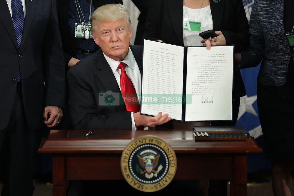January 25, 2017 - Washington, District of Columbia, U.S. - United States President DONALD TRUMP (C) displays one of the two executive orders he signed during a visit to the Department of Homeland Security. Trump signed two executive orders related to domestic security and to begin the process of building a wall along the U.S.-Mexico border.  (Credit Image: © Chip Somodevilla/Pool/CNP via ZUMA Wire)