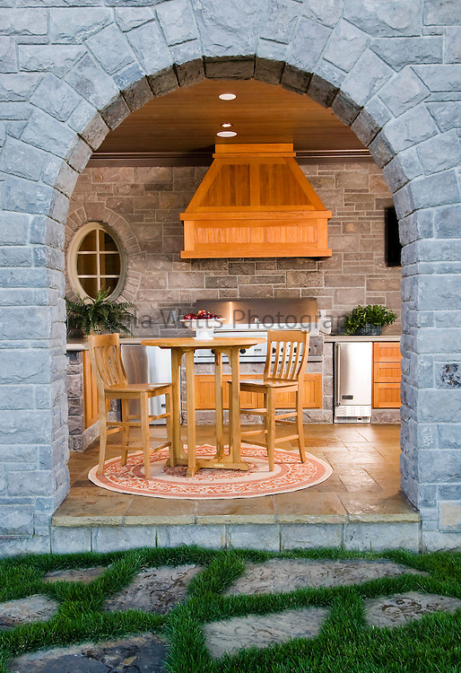 Outdoor kitchen with grill and seating with elegant stone archway and wood accents