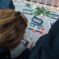 Participant takes a photo with her mobile as others light candles in support for the terrorist attack victim staff of the Charlie Hebdo satirical weekly in Budapest, Hungary on January 08, 2015. ATTILA VOLGYI