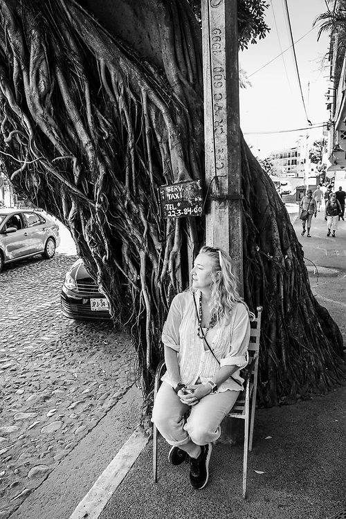 A woman sits in a chair on the street in Puerto Vallarta, Mexico waiting for a taxi.