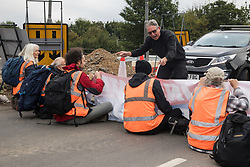 An angry motorist points at Insulate Britain climate activists blocking a slip road from the M25 at Junction 25 as part of a campaign intended to push the UK government to make significant legislative change to start lowering emissions on 15th September 2021 in Enfield, United Kingdom. The activists, who wrote to Prime Minister Boris Johnson on 13th August, are demanding that the government immediately promises both to fully fund and ensure the insulation of all social housing in Britain by 2025 and to produce within four months a legally binding national plan to fully fund and ensure the full low-energy and low-carbon whole-house retrofit, with no externalised costs, of all homes in Britain by 2030 as part of a just transition to full decarbonisation of all parts of society and the economy.
