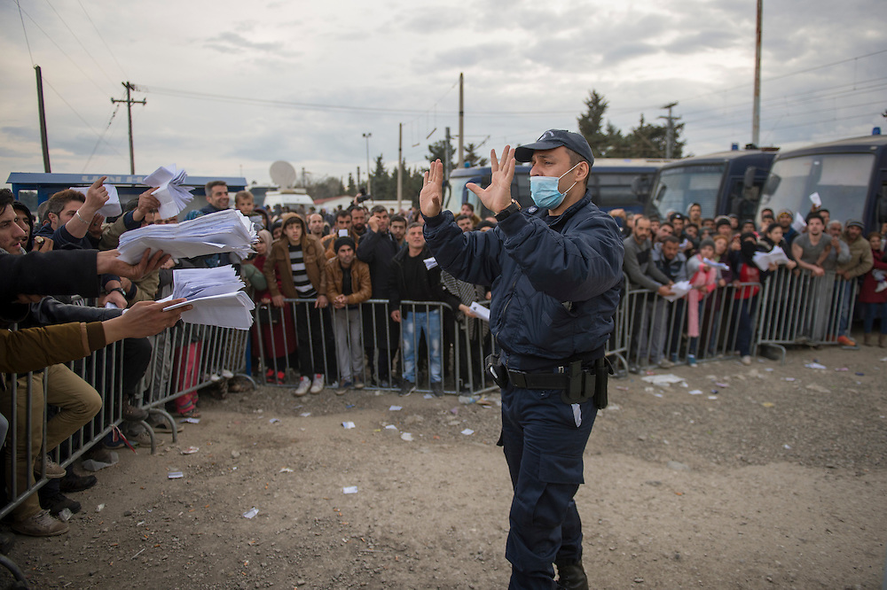 March 3, 2016, Idomeni, Greece. A Greek police man refuses the papers that are held to him by refugees who hope to get on a waiting list to cross the border. Only a few get through every day and can continue their journey to Western Europe.   12.000 refugees are stuck at the Idomeni border crossing in Greece  after Macedonia closed the border.  New arrivals come in every day, making living conditions difficult.(Steven Wassenaar/Polaris)