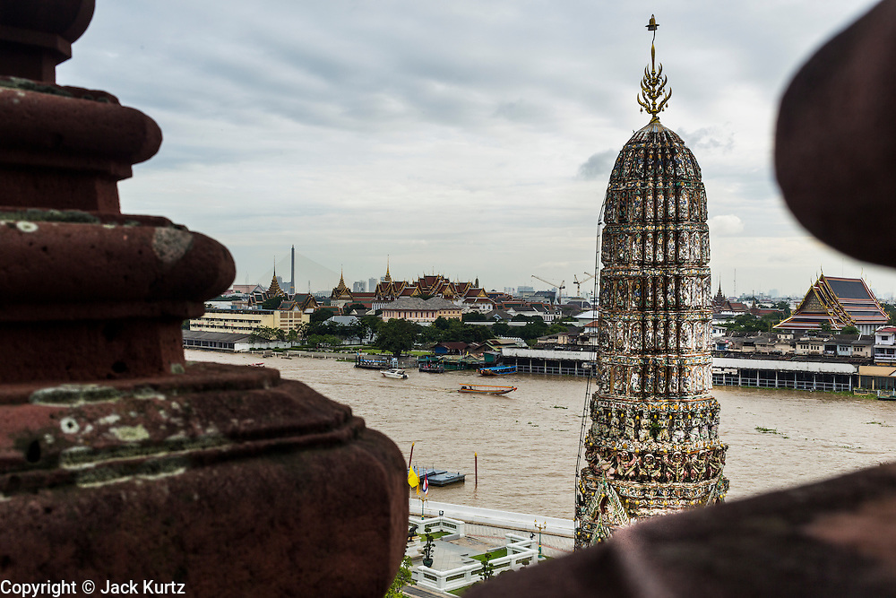 """23 SEPTEMBER 2013 - BANGKOK, THAILAND:     A satellite prang the supports the famous central prang at Wat Arun with the Chao Phraya River the city of Bangkok in the background. The full name of the temple is Wat Arunratchawararam Ratchaworamahavihara. The outstanding feature of Wat Arun is its central prang (Khmer-style tower). The world-famous stupa, known locally as Phra Prang Wat Arun, will be closed for three years to undergo repairs and renovation along with other structures in the temple compound. This will be the biggest repair and renovation work on the stupa in the last 14 years. In the past, even while large-scale work was being done, the stupa used to remain open to tourists. It may be named """"Temple of the Dawn"""" because the first light of morning reflects off the surface of the temple with a pearly iridescence. The height is reported by different sources as between 66,80 meters and 86 meters. The corners are marked by 4 smaller satellite prangs. The temple was built in the days of Thailand's ancient capital of Ayutthaya and originally known as Wat Makok (The Olive Temple). King Rama IV gave the temple the present name Wat Arunratchawararam. Wat Arun officially ordained its first westerner, an American, in 2005. The central prang symbolizes Mount Meru of the Indian cosmology. The temple's distinctive silhouette is the logo of the Tourism Authority of Thailand.       PHOTO BY JACK KURTZ"""