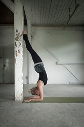 Mid adult woman practicing handstand in yoga studio, Munich, Bavaria, Germany