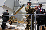 A soldier from the British Royal Artillery guards a 12ft Fire Shadow missile on manufacturer MBDA's trade stand at the Farnborough airshow, shows visiiting guests to this exhibit the merits of its use and design. The so-called lurker bomb is designed to loiter above a battlefield for up to 6 hours before attacking stationary or mobile targets and also able to shadow British troops for up to ten hours or 100 miles, ready to take out enemy targets with surgical precision at a minute's notice. . The Farnborough International Airshow is a seven-day international trade fair for the aerospace industry and held every two years in mid-July at Farnborough Airport in Hampshire, England known as the home of British aviation, held since there since 1948. The show is usually attended by more than 1,300 exhibitors and 150,000 trade visitors.
