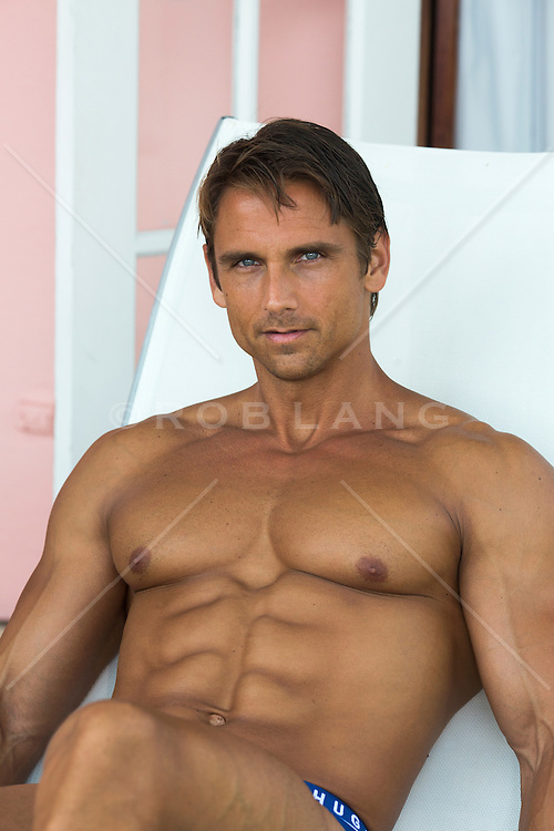 handsome All American man with a great body lounging in a chair outdoors