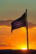 Sunset behind American Flag waving in the breeze  near Winslow, Arizona