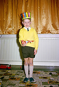 Young boy wearing yellow jumper and Red Indian hat playing with red space rocket toy on Christmas morning, British culture 1967