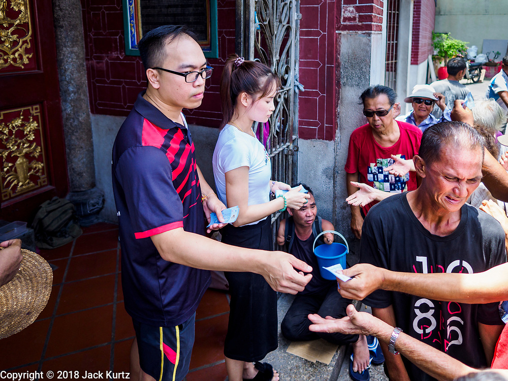 25 AUGUST 2018 - GEORGE TOWN, PENANG, MALAYSIA: People hand out cash to the poor at Kuan Yin Temple on Ghost Day, the full moon day (or night) that falls in the middle of Hungry Ghost month. The Ghost Festival, also known as the Hungry Ghost Festival is a traditional Taoist and Buddhist festival held in Chinese communities throughout Asia. Ghost Day, is on the 15th night of the seventh month (25 August in 2018). During Ghost Festival, the deceased are believed to visit the living. In many Chinese communities, there are Chinese operas and puppet shows and elaborate banquets are staged to appease the ghosts.       PHOTO BY JACK KURTZ