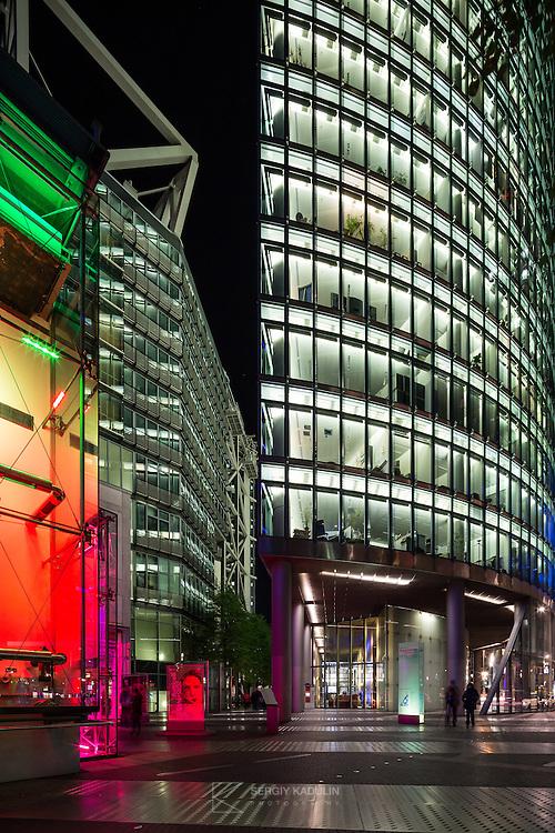 Modern office building at night on Potsdamer Platz, Berlin. Vertical format.