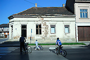Man and children crossing street, building with bullet holes in wall from 1991 -- 1995 war. Petrinja, Croatia
