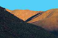 Alpenglow paints warm light on a ridge of the San Ysidro Mountains, Anza-Borrego desert, California, USA.