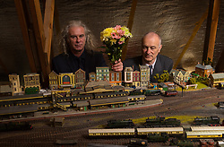 Brothers Simon, 53 and Paul Hurst, 58 have some of their late father's ashes carried around his extensive model railway in the loft of his home. PICTURED: Simon, left and Paul Hurst pose with a bunch of flowers in the loft of their late father Peter's home where he built a complex and highly detailed model railway. Leeds, Kent, March 15 2018.
