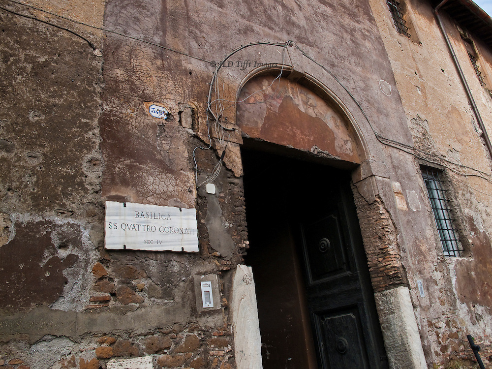 SS Quattro Coronati, exterior, entrance, patched with cement and draped informally with electrical wiring.
