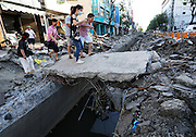 KAOHSIUNG, CHINA - AUGUST 04: (CHINA OUT) <br /> <br /> Gas Explosion Rips up entire road in china<br /> <br /> People walk on a huge stone to pass the broken road after Kaohsiung\'s gas explosion on August 4, 2014 in Kaohsiung, Taiwam of China. Part of the pipeline was found wornout after 4 days of investigations. <br /> ©Exclusivepix