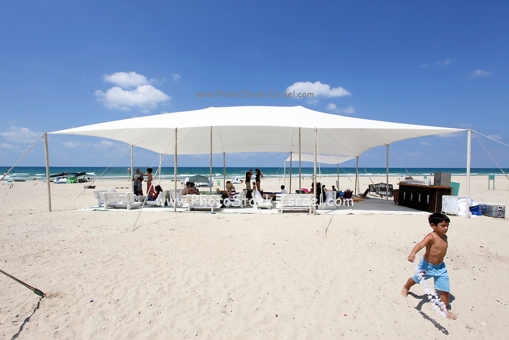 Israel, Mediterranean sea, Temporary seaside cafe a shade net, deck chairs and cushions