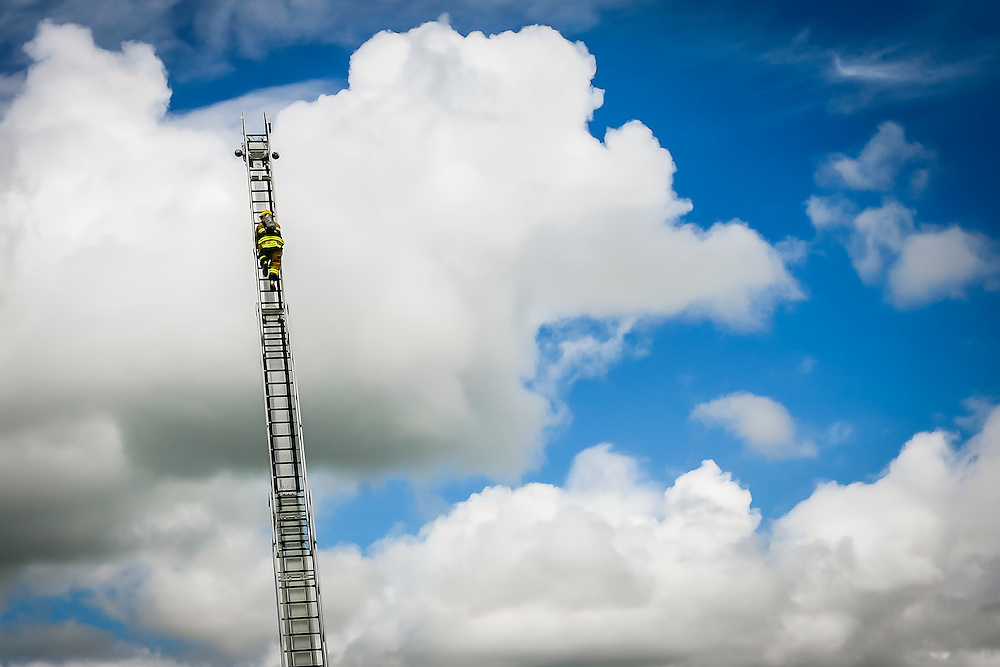 Bonita Springs Fire Control & Rescue District probationary firefighter Andy Schmidt climbs to the top of a 65 foot ladder during a ladder truck training exercise for new recruits, Tuesday, at the training facilities of Station Number Four in Bonita Springs. Schmidt is one of seven probationary firefighters who will join the fire department on Sept. 15 after four weeks of orientation training.  David Albers/ Staff.
