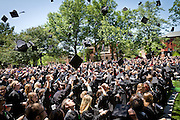 Grinnell students toss their graduation caps into the air during Commencement. BEN BREWER/Grinnell College