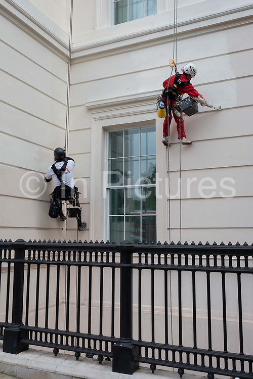 Abseiling painters put a fresh coat of colour on the exterior of the Laneborough Hotel at Hyde Park Corner, on 8th June 2018, in London, England.