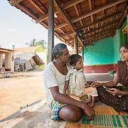 CAPTION: Gathering community data. Mobility India and CBM have partnered with Aptivate to develop a simple means of collecting key project-relevant data using relatively unsophisticated mobile phones. LOCATION: Sappayyanapura (village), Kasaba (hobli), Chamrajnagar (district), Karnataka (state), India. INDIVIDUAL(S) PHOTOGRAPHED: From left to right: Mariswamy, Manu and Nandini A.C.