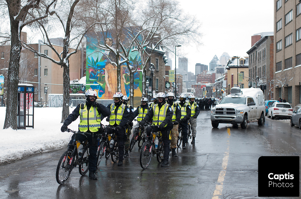 Police wait for protesters to march in downtown Montreal. March 15, 2015