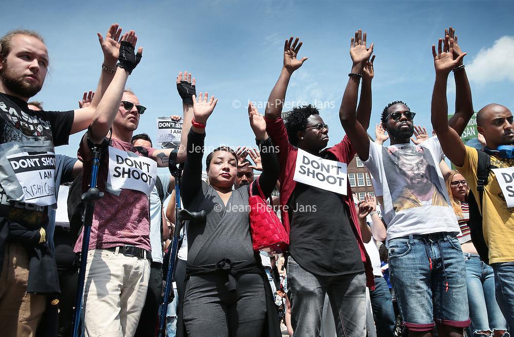 """Nederland, Amsterdam, 10 juli 2016<br /> Een paar honderd mensen zijn vanmiddag op de Dam in Amsterdam bijeen gekomen om in stilte te protesteren tegen het politiegeweld in Amerika. Onder de naam Black Lives Matter trok de stoet vervolgens door de stad.<br /> """"Mijn initiatief was om alleen op de Dam te gaan staan met een papiertje op mijn rug"""", vertelt initiatiefneemster Anna Hammond.""""Eniedereen die langs komt kon dan vragen aan mij stellen, en ik zou die vragen dan beantwoorden.""""<br /> """"Ik heb dat op mijn Facebook gepost, omdat ik dacht: ja misschien willen wel wat vrienden meedoen. En dat is viral gegaan. Ik had nooit gedacht dat er zo veel mensen op af zouden komen"""",zegt ze verrast.<br /> <br /> Netherlands, Amsterdam, July 10, 2016<br /> A few hundred people met this afternoon on the Dam in Amsterdam to protest silently against police violence in America. Under the name Black Lives Matter the procession continued through the city.""""My initiative was to just stand on the Dam with a piece of paper on my back,"""" says initiator Anna Hammond. """"And everyone who comes along could then ask me questions, and I would answer those questions.""""I've posted on my Facebook, because I thought, yeah maybe do want to join some friends and that went viral. I never thought that so many people would join,"""" She says surprised.<br /> <br /> Foto: Jean-Pierre Jans"""