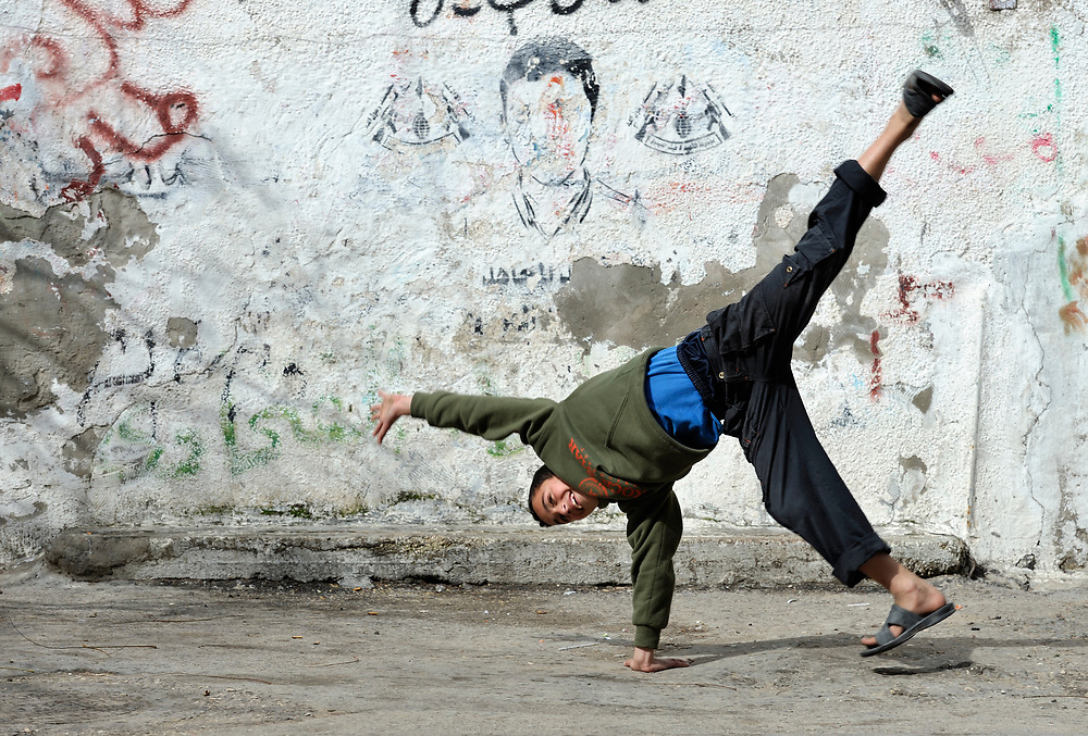 A boy does a cartwheel in the Nuseirat refugee camp in the middle of the Gaza strip. .