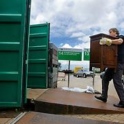Nederland Hoogvliet gemeente Rotterdam 16 juni 2012 20120616  Milieupark Hoogvliet, op het afvalaanbiedstation kunnen afvalstoffen afkomstig van particuliere huishoudens worden aangeboden. Een man biedt kastje aan. Hij brengt dit meubel naar de container van kringloopgoederen, bedoelt om opieuw gebruikt te wordewn.  Garbage disposal, enviroment, enviromental, green initiative Foto: David Rozing