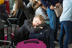 A boy sleeps using his suitcase as a pillow at Terminal 5 at Heathrow Airport after an IT glitch brings British Airways systems to a halt, causing disruption to thousands of passengers with flights cancelled and delayed. London, August 07 2019.
