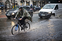© Licensed to London News Pictures. 14/09/2021. London, UK. A cyclist ploughs through surface water on the Euston road in North London during heavy rainfall. Heavy rain is expected to cause flash flooding in parts of the UK. Photo credit: Ben Cawthra/LNP