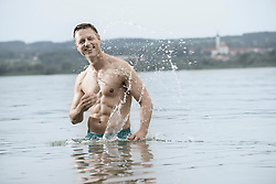 Mature man in lake with full of splash, Bavaria, Germany