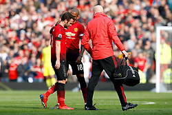 Manchester United's Juan Mata (left) is comforted by team mate Ashley Young after picking up an injury during the Premier League match at Old Trafford, Manchester.