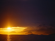 Sun shining beneath storm clouds and illuminating foothills of the Fairweather Range, Outer Coast of Glacier Bay National Park, Alaska.
