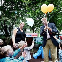 Nederland, amsterdam , 26 juli 2011..Kinderdagverblijf Kinderheuvel (het vroegere Hofnarretje) in de van Woustraat viert feest..Op de foto directeur Henk Lustig deelt ballonnen uit aan kinderen van het kinderdagverblijf. op de achtergrond en links enkele peuterleidsters en ouders..Foto:Jean-Pierre Jans