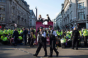 Metropolitan and other police officers prepare to remove and arrest Extinction Rebellion activists who had taken part in a pink roadblock of Oxford Circus by women and FINT-identifying environmental activists during the third day of Impossible Rebellion protests on 25th August 2021 in London, United Kingdom. Extinction Rebellion are calling on the UK government to cease all new fossil fuel investment with immediate effect.