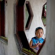 Small girl peeks through window in double lane corridor (Shanghai, China - Sep. 2008) (Image ID: 080927-1138091a)