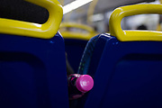 A pink-topped plastic bottle is wedged between seats on the top deck of a London bus, on 20th November 2019, in London, England.