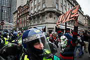 Protester wearing a silver skeleton mask holds a sign saying LOVE at riot police. Anti capitalists / anarchists go on the rampage through central London on the back of the peaceful TUC protest march. The masked demonstrators ran a twisting route through the capital confusing the police and creating a situation which was very difficult to manage. The protesters attacked banks, shops and hotels, and the police in riot gear fought  face to face with them as they were pelted with ammonia, paint and fireworks loaded with coins.