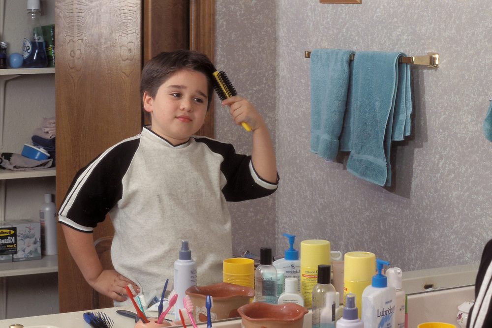 2nd grade boy looks in mirror while brushing hair at home in bathroom.  Model Release.<br /> ©Bob Daemmrich