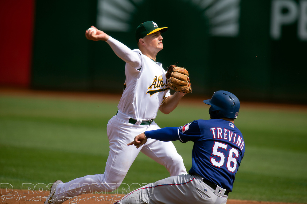 Oakland Athletics third baseman Matt Chapman (26) throws over Texas Rangers' Jose Trevino (56) to complete a double play during the second inning of a baseball game, Sunday, Sept. 22, 2019, in Oakland, Calif. Texas Rangers Shin-Soo Choo was out at first base. (AP Photo/D. Ross Cameron)