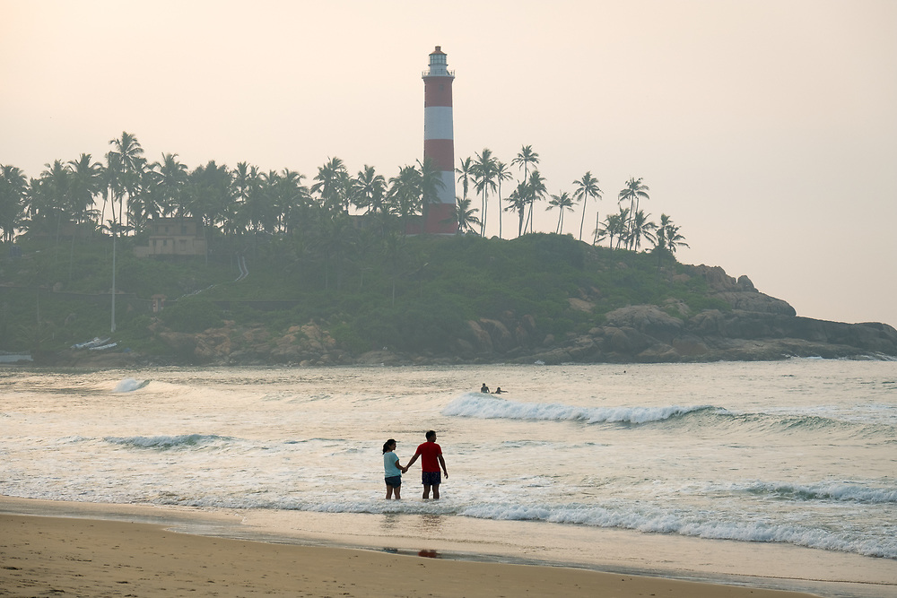 A couple on the beach of Kovalam in Kerala is waiting for sunrise.
