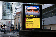 With local coronavirus lockdown measures in place and Birmingham currently set at 'Tier 2' or 'high', Public Health England / NHS digital information poster advises people to only get a coronavirus test if they are showing symptoms, in city centre on 26th October 2020 in Birmingham, United Kingdom. The three tier system in the UK has levels: 'medium', which includes the rule of six, 'high', which will cover most areas under current restrictions; and 'very high' for those areas with particularly high case numbers. Meanwhile there have been calls by politicians for a 'circuit breaker' complete lockdown to be announced to help the growing spread of the Covid-19 virus.