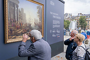 Members of the public admire a copy of 'Seaport with the Embarkation of Saint Ursula' by Claude Lorrain (1641), part of a temporary display of historical art placed outside the National Gallery to show passers-by what can be seen in their galleries, on 1st September 2021, in Trafalgar Square, London, England.